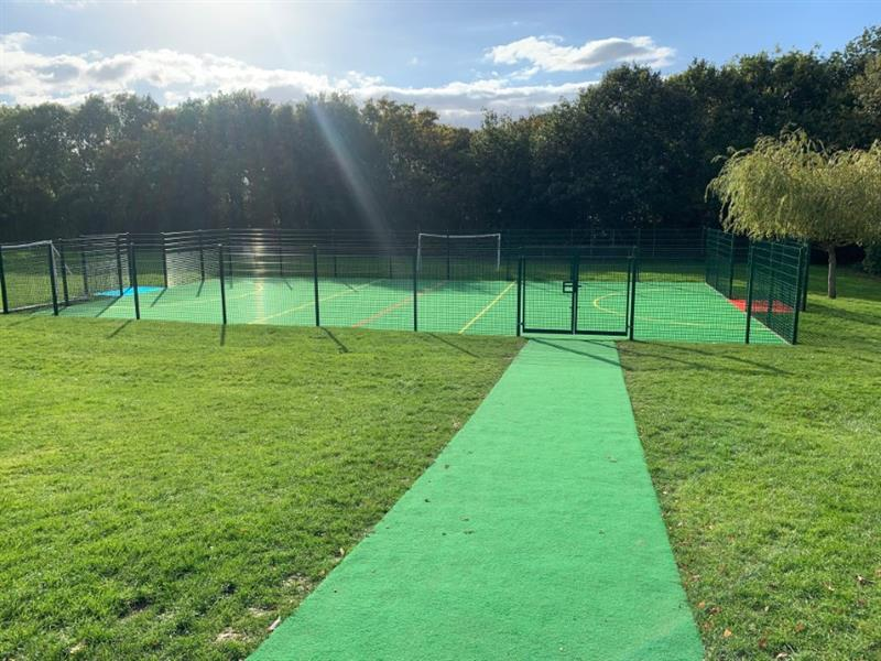 An artificial grass pathway leading to a muga pitch