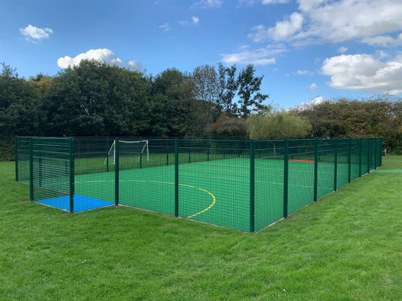 A muga pitch with sport fencing and blue recessed goal end