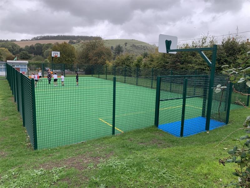 Pentagon Play's MUGA pitch that has been installed onto grass with rebound fencing and all-weather surfacing.