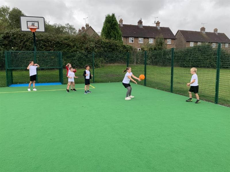 A child catching a basketball while playing with others on the school's muga pitch