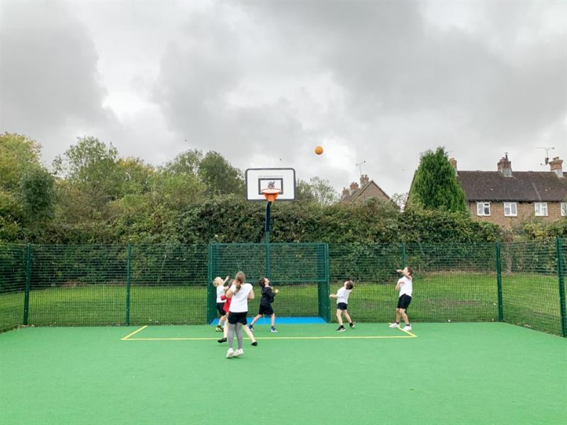 Children playing basket ball on a multi use games area