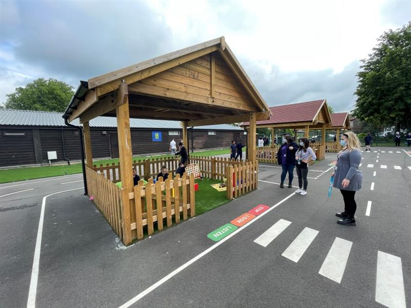 3 of our outdoor classrooms with children playing inside them and on the roadway. 3 adults are accompanying the children who are stood on the roadway.