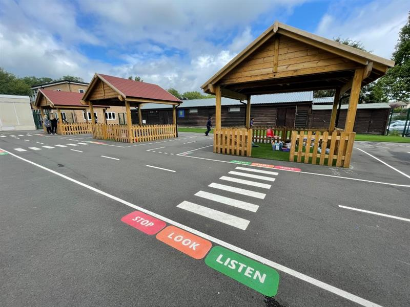 Three wooden outdoor classrooms. Zebra crossings are running through the roadway that surrounds them, with stop, look and listen signs.
