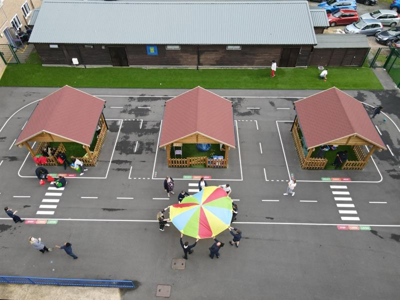 A birds eye view of 14 children playing in and around 3 of our outdoor classrooms, 7 children and 1 adult are playing with a parachute next to wooden outdoor classrooms.