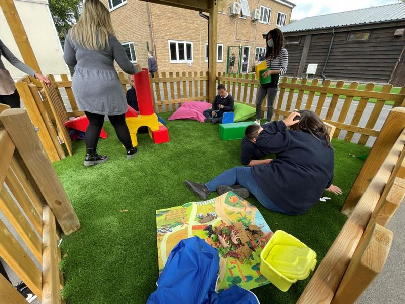 3 children and 3 adults are playing in a Pentagon Play outdoor classroom with artificial grass flooring.. The children are playing with building blocks.