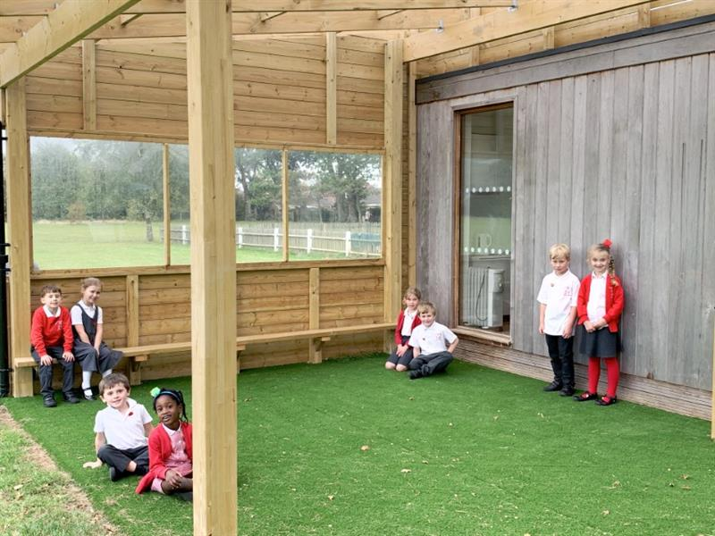 Children sitting under a timber canopy smiling at the camera
