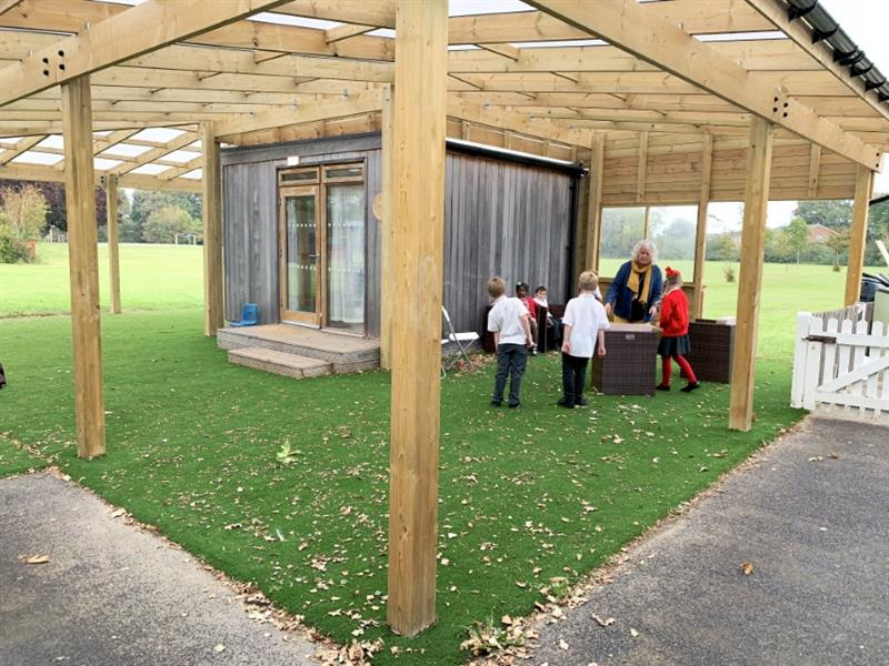 a group of children and a teacher underneath a timber canopy talking