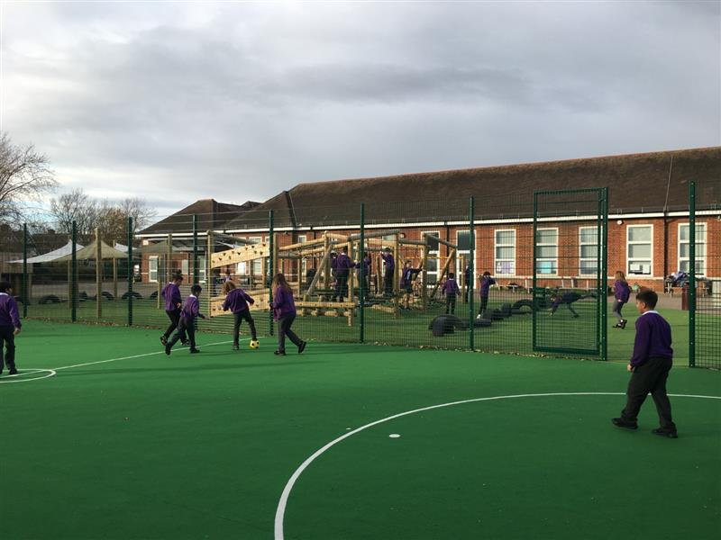 6 children playing football on a muga pitch installed onto the school playground