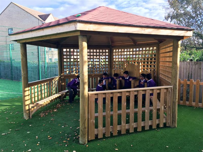 4 children sat inside of a timber outdoor classroom talking with one another