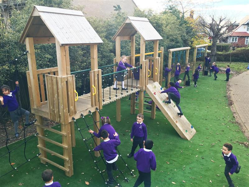 An overhead view of a 20 piece modular play tower installed alongside a hedge row on the school playground