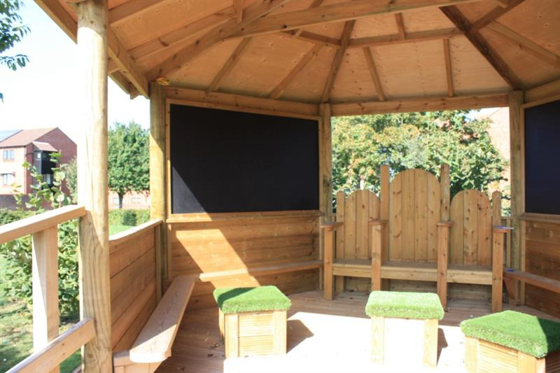 inside of an outdoor classroom with a chalkboard and movable grass topped seats