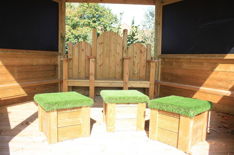 a close up photo inside the outdoor classroom showing movable grass topped seats and fixed seating.