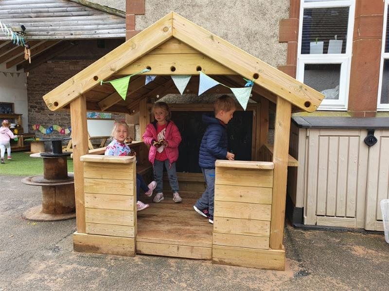 Children playing inside a small playhouse