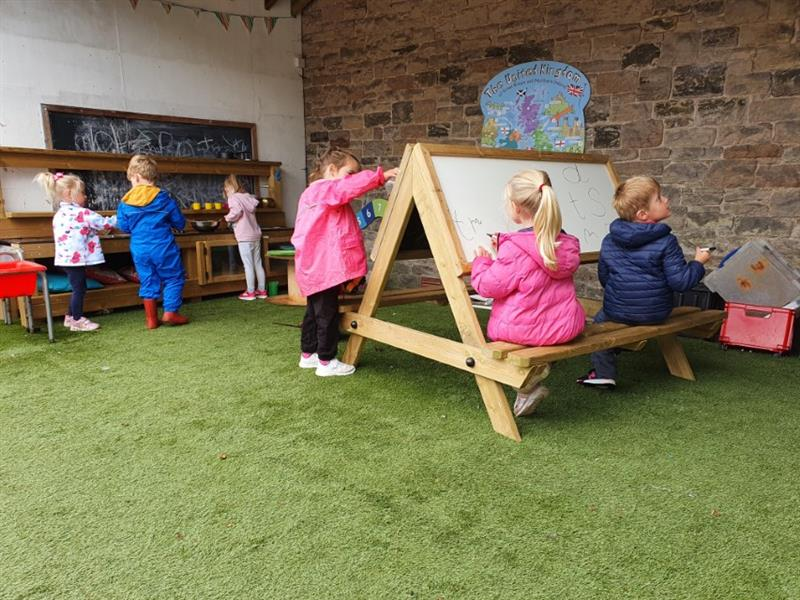children sat drawing on an easel table placed on top of artificial grass