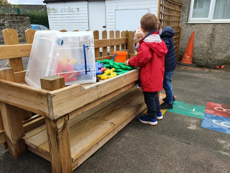 Children playing with construction toys on a construction table on the playground