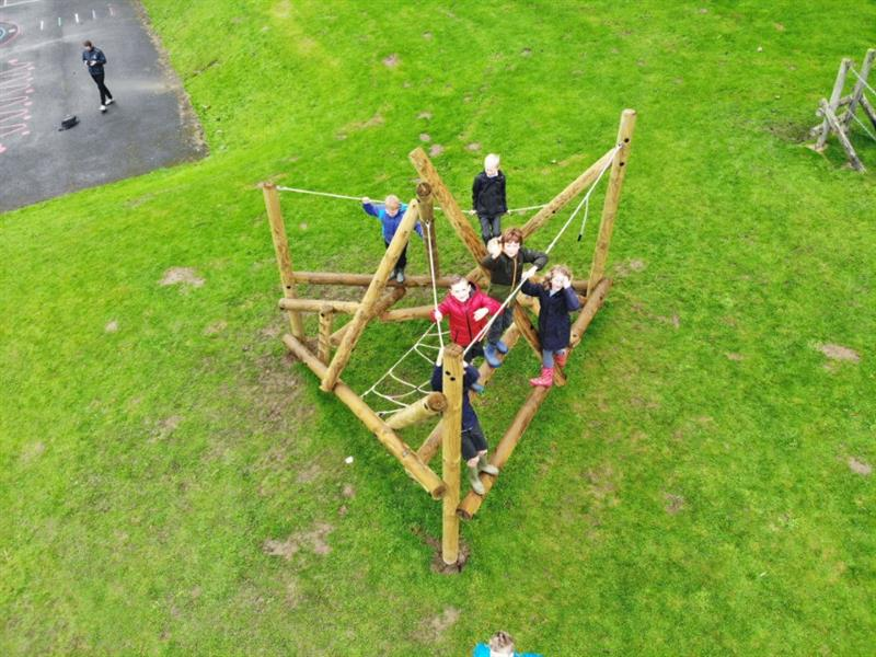 6 children climbing on a log and rope climbing frame