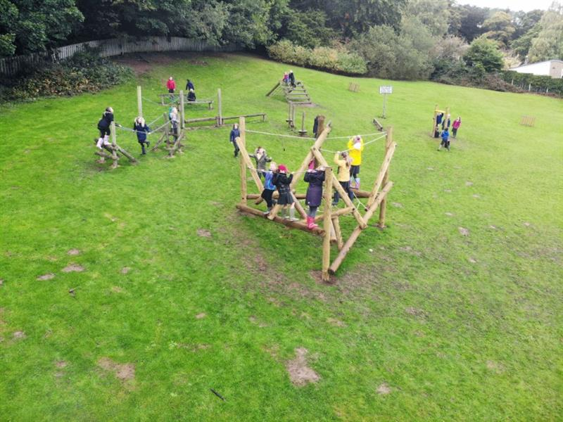 Children playing on active play equipment on the school field