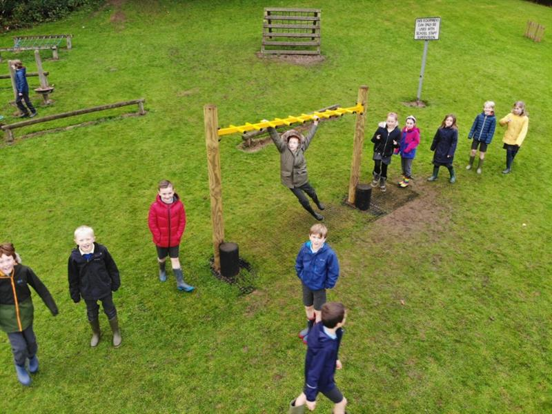Children lining up to cross monkey bars on the field