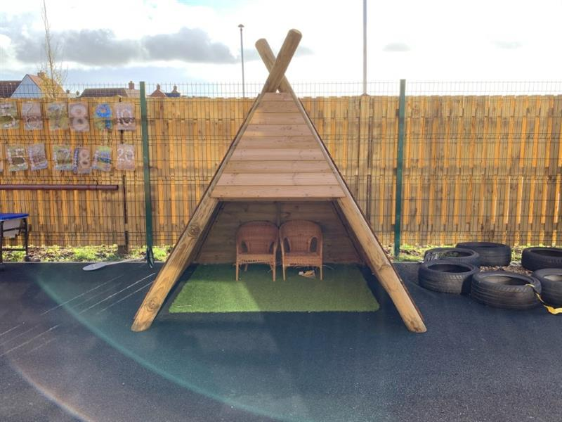A Wigwam Den with two wicker chairs and artificial grass inside