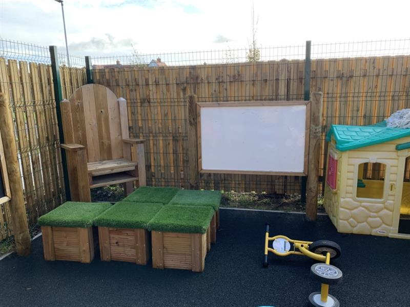 A storytelling chair, movable grass topped seats and giant whiteboard