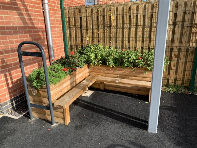 A corner planter bench with various plants growing