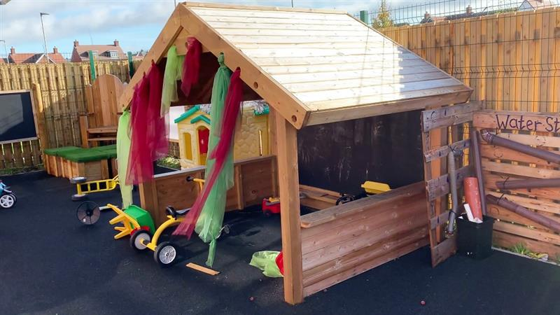 A giant playhouse with material hanging from the den making holes