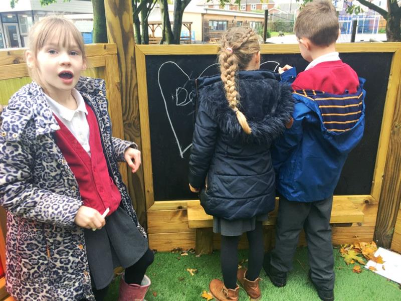 Children writing on a chalkboard in an imagination station