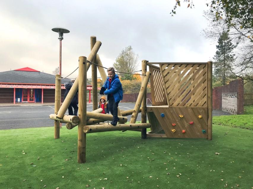 A log climbing frame installed onto artificial grass playground surfacing