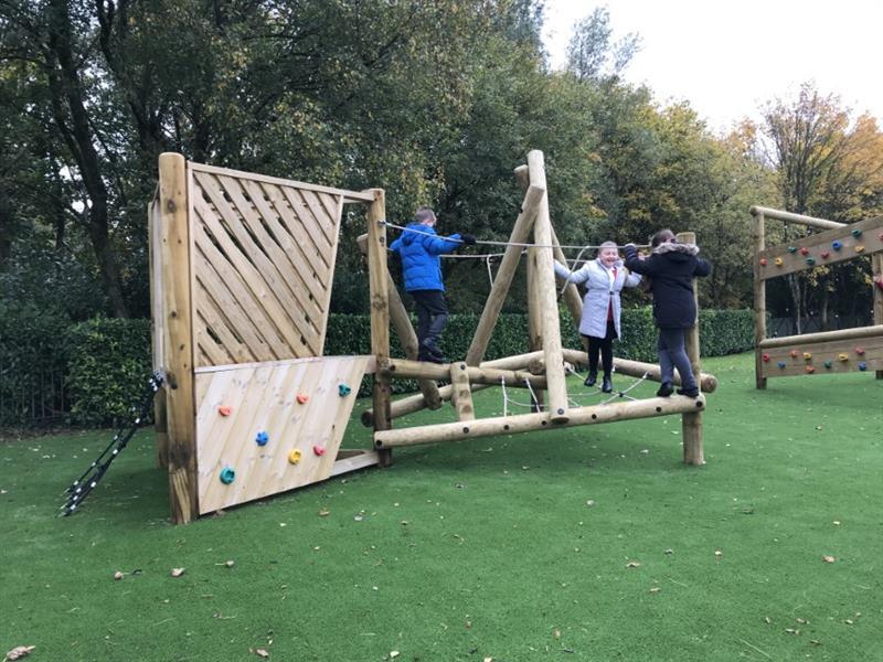KS1 children climbing on a log climbing frame