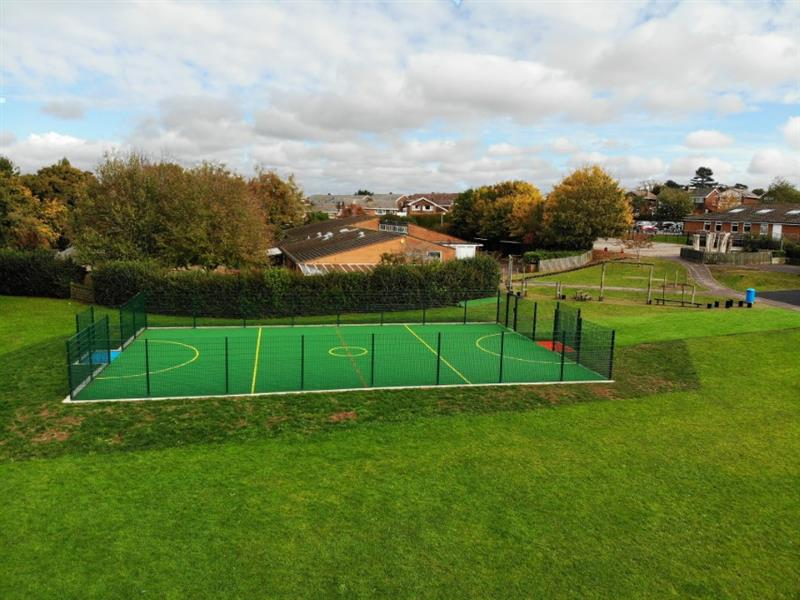 A multi use games area installed onto a school field with 2m high fencing, yellow sport markings and a red goal end and a blue goal end