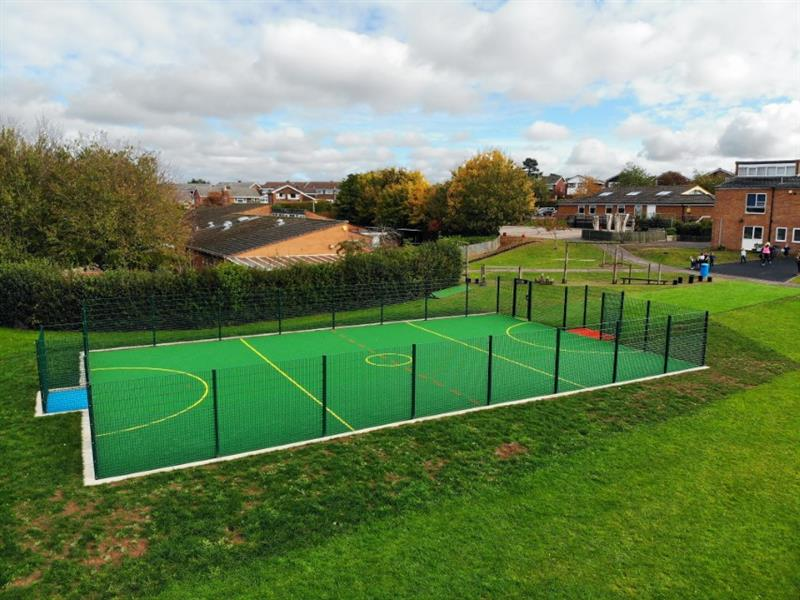Raysfield Primary School's MUGA pitch installed onto their school field featuring yellow sport markings, fencing and recessed goal ends