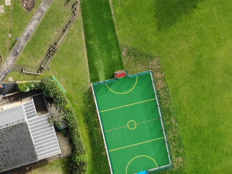 An overhead view of a multi use games area with yellow sport markings, fencing, a red goal end, a blue goal end and a 8m artificial grass pathway from the playground