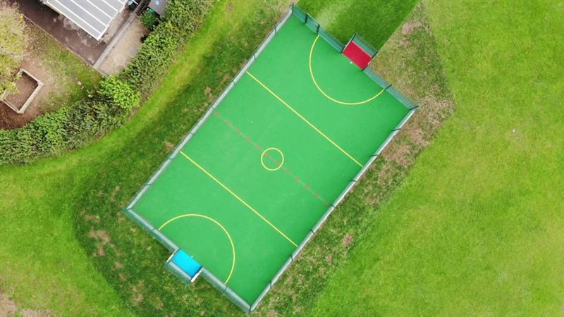 An overhead view of a multi use games area featuring yellow sport markings, 1 blue goal end, 1 red goal end and an artificial grass pathway to the playground