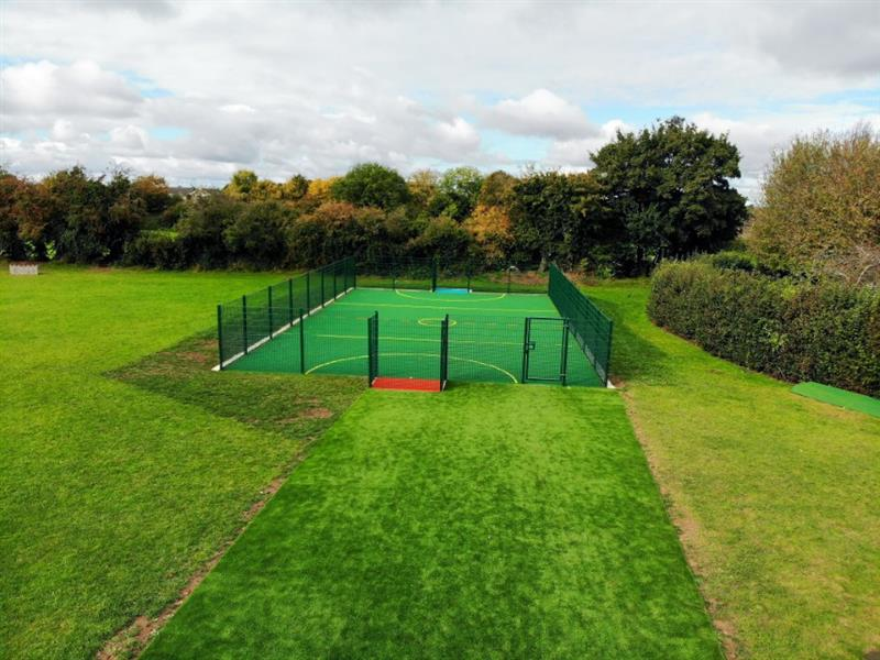 An 8m wide artificial grass pathway leading to the access gate of a multi use games area