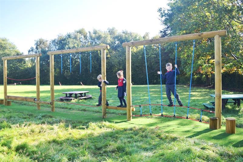 Children using a school playground trim trail that has been installed onto a school field
