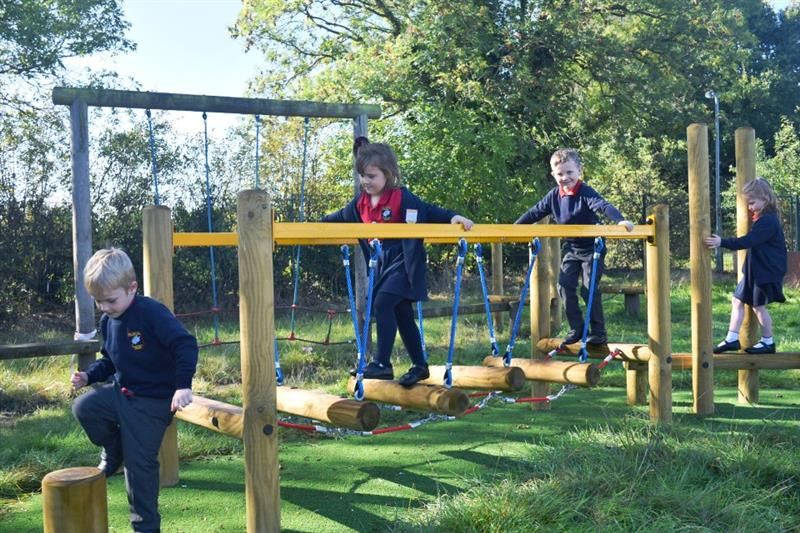 Children using trim trail equipment on their school playground, moving across a wobbly bridge onto a stepping log