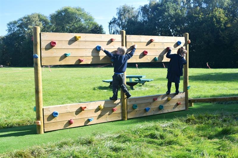 Children climbing on a climbing wall installed onto a school field