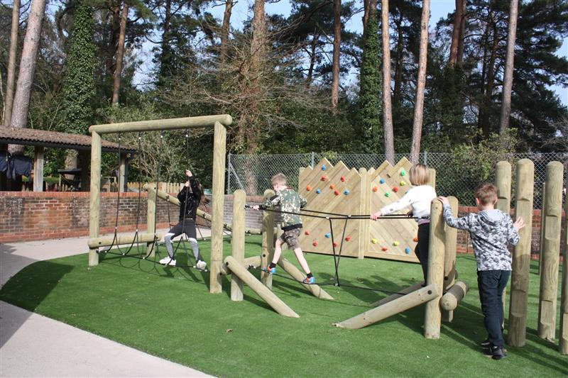 children tackling forest trim trail obstacles as they move through the challenges featured