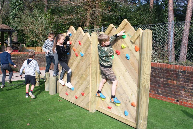 two children moving across a forest climbing wall installed onto artificial grass