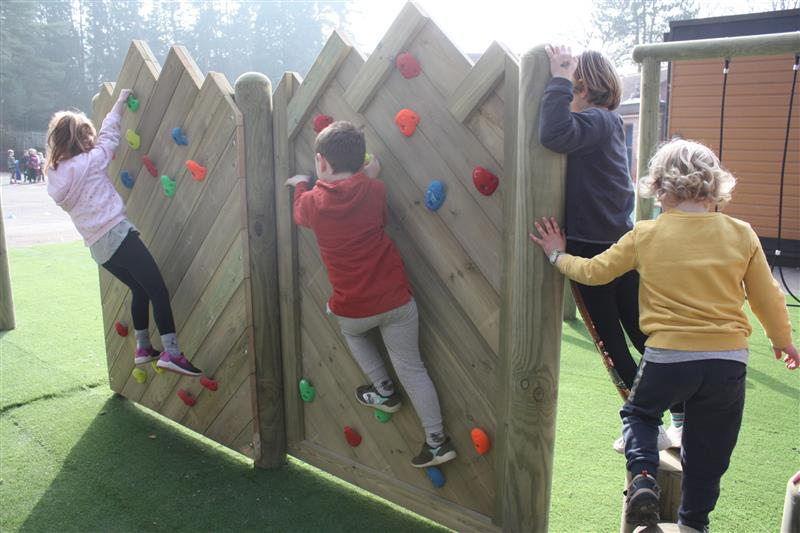 Two children climbing across a double sided forest climbing wall