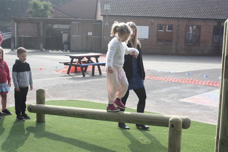 A child balancing across an inclined balance beam