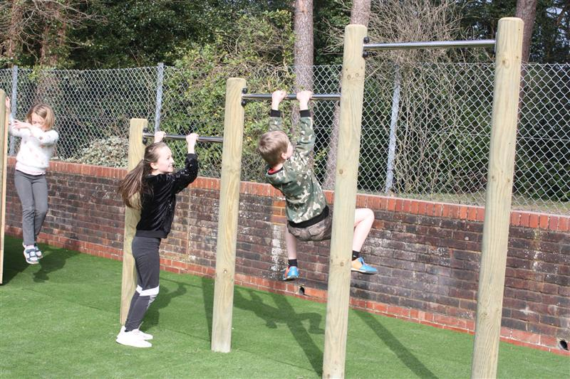 two children seeing how many pull ups they can do on a set of pull up bars