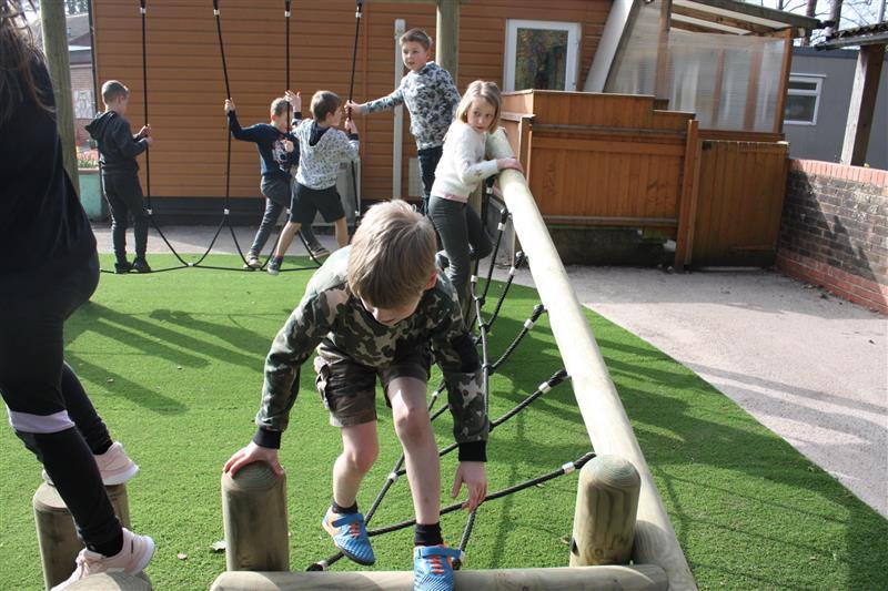Children climbing on forest school trim trail equipment