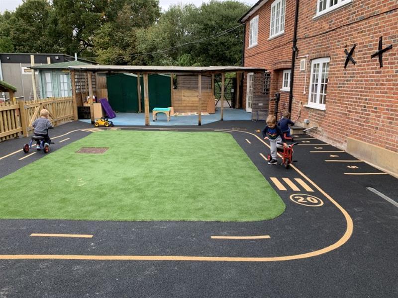 Toddlers racing trikes around a nursery garden roadway