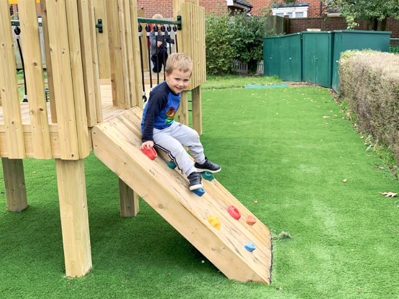 Toddler climbing up a playground tower climbing ramp