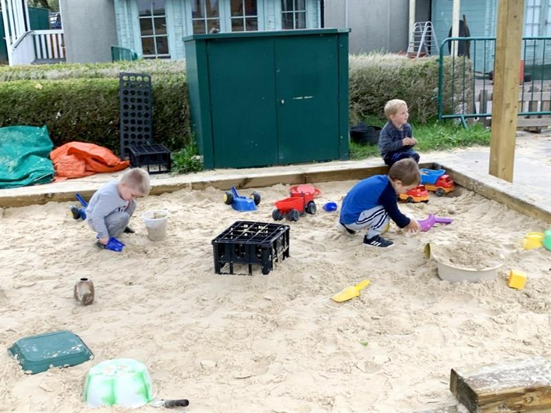 Toddlers playing in a bespoke built sand pit