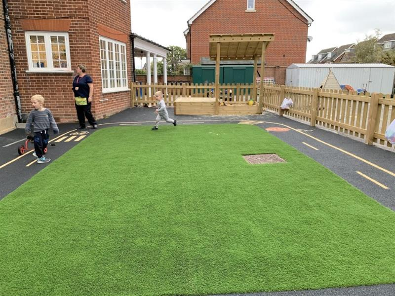 Toddlers running around on artificial grass surfacing