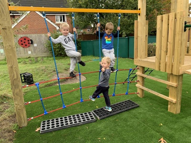 Toddlers playing on a play tower in the nursery garden