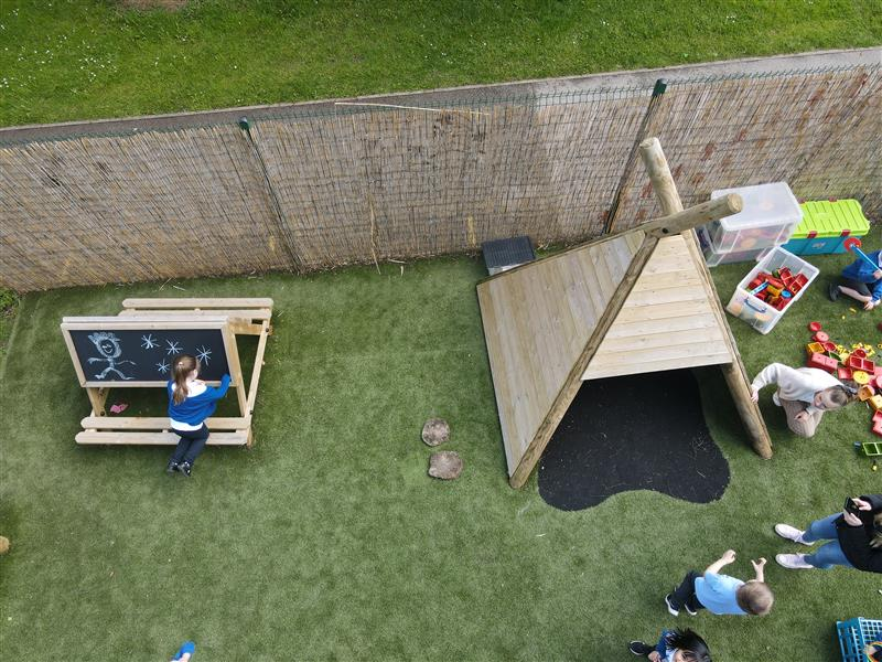 children playing on in our wigwam and a girl drawing on chalk board