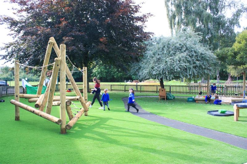 Children playing on artificial grass playground surfacing